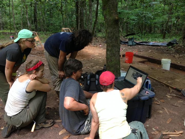Dr. Birch and field school students look at geophysical data from Singer-Moye