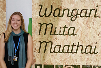 Katie Gibson standing next to name of Kenyan Nobel laureate