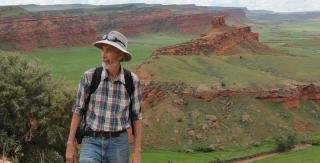 Archaeologist Robert Kelly stands before dramatic mesas