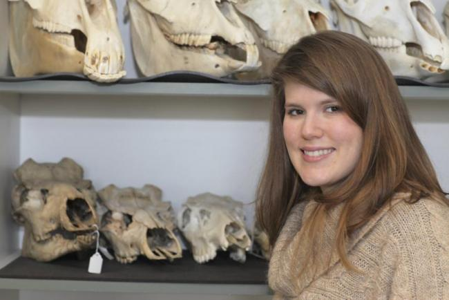 Suzanne Pilaar Birch stands in front of a shelf holding animal skulls