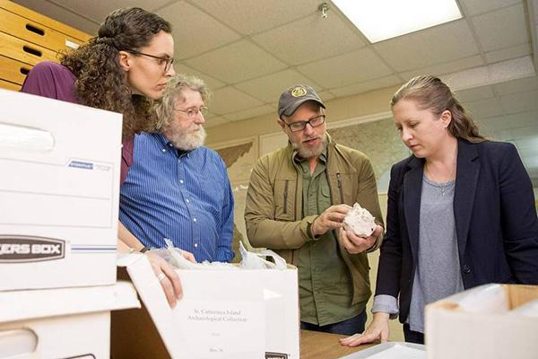 members of the UGA archaeology department and the lab director of the Nels Nelson North American Archaeology Laboratory at the American Museum of Natural History examine artifacts from the collection